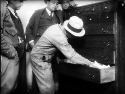 Miembro del Ministerio Público realizando investigaciones en el cajón de un ropero