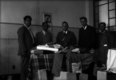 Agentes del Ministerio Público y otros hombres junto a rollos de tela decomisados