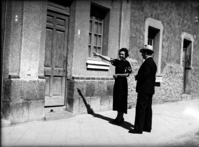 Mujer señalandole la entrada de un edificio a un miembro del ministerio público