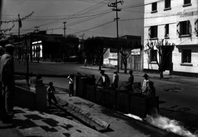 Hombres observan el desemboque de un acueducto en la calle 5 de mayo