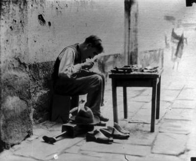 Zapatero trabajando en la calle