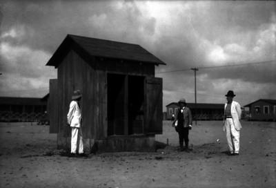 Norberto Domínguez, ingeniero, y otros hombres mostrando los baños en una zona petrolera