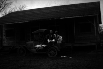 Petroleros junto a un automóvil frente a una cabaña, retrato