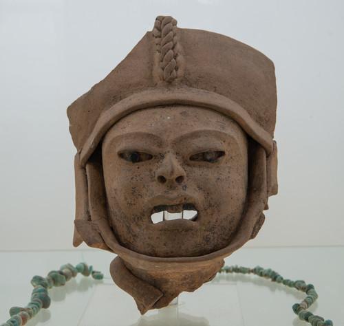 Cabeza escultura hueca de barro con tocado y banda en el maxilar