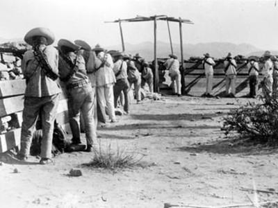 Revolucionarios detras de una trinchera, apuntan con sus rifles