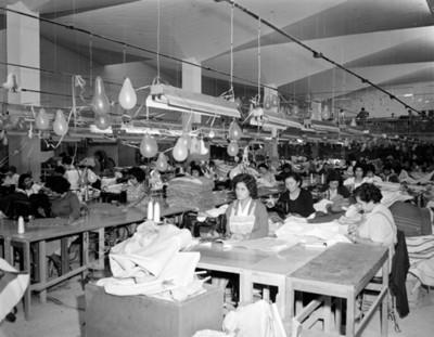 Mujeres operan máquiba de coser en una fábrica textil