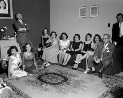 Mujeres y hombres durante reunión en la sala de una casa, retrato de grupo