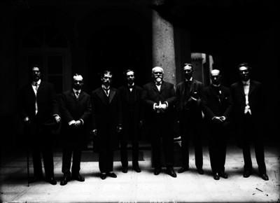 Justo Sierra Méndez acompañado por hombres a las afueras de un edificio, retrato