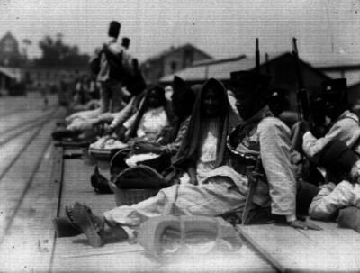 Federales y familiares en el techo de los vagones de un tren