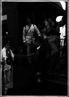 Soldados federales, soldaderas y administrador del ferrocarril, en el estribo de un vagón, retrato de grupo