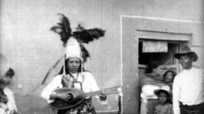 Conchera tocando una guitarra fuera de un comercio