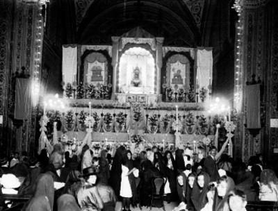 Gente durante celebración religiosa ante el altar mayor de una iglesia