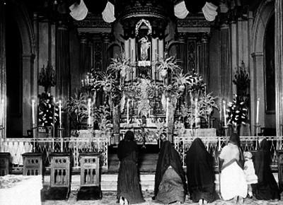 Mujeres hincadas ante altar mayor de una iglesia del siglo XIX