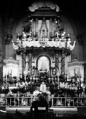 Mujer reza ante altar mayor de una iglesia del siglo XIX