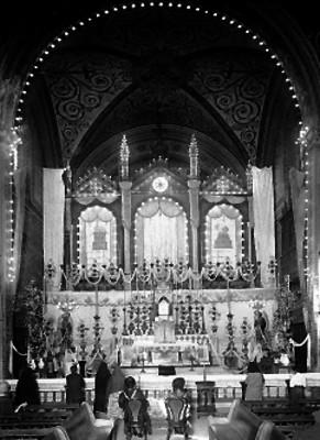Feligreses ante altar mayor de una iglesia