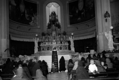 Gente presente en una iglesia, frente al altar mayor del siglo XIX