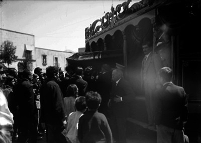Personas observan la introducción de un féretro a una carroza