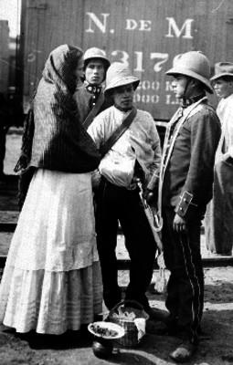 Soldados federales conversan con una mujer en una estación de ferrocarril