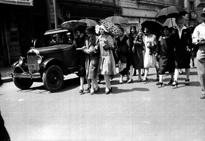 Mujeres con sombrillas caminan por la calle