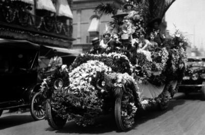 Gente con trajes regionales en un carro alegórico, durante un desfile