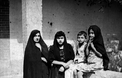 Mujeres y niños sentados en una barda, retrato