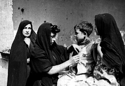 Mujer arreglandole la ropa a un niño