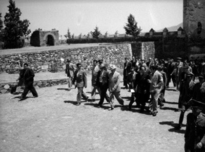 Harry S. Truman acompañado por funcionarios durante un recorrido por el patio de un convento del siglo XVI