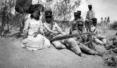 Revolucionarios villistas y mujer humilde en un campo, retrato de grupo
