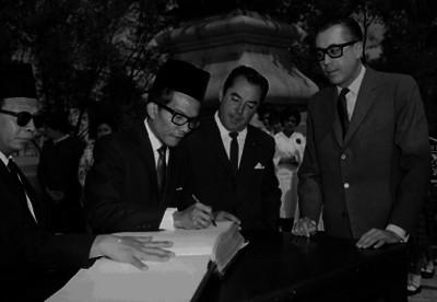 Joaquín Bernal García Pimentel viendo a un diplomático extranjero firmar el libro de visitantes distinguidos
