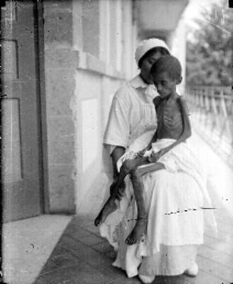 Enfermera carga a niño desnutrido en el pasillo de un hospital