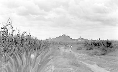 Mujeres indígenas en un camino, al fondo la iglesia de Nuestra Señora de los Remedio