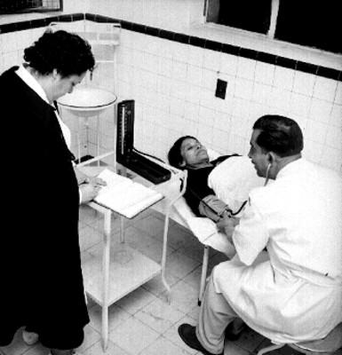 Médico ausculta a anciana en el consultorio de un albergue