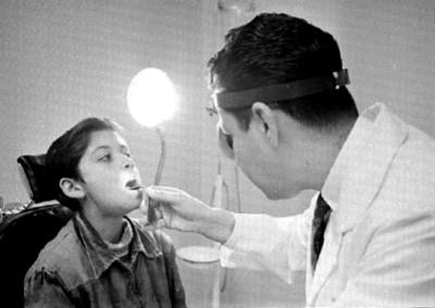 Médico revisa la boca de un niño enfermo de audición