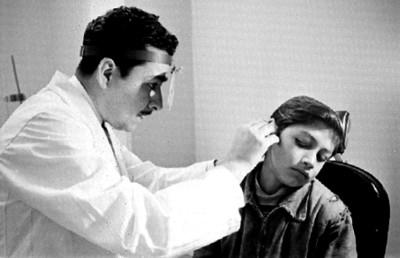 Médico examina el oído a niño