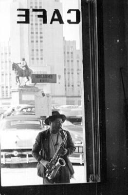 Músico callejero toca saxofón afuera de una cafetería