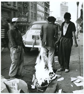 Voceadores prenden fuego a periódicos en una calle