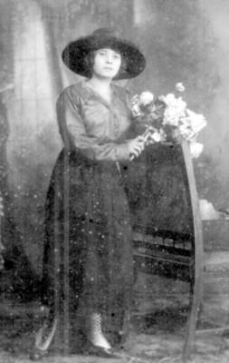 Mujer con ramo de flores de pie junto a una silla, retrato
