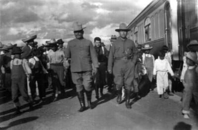 Alvaro Obregón y su séquito paseando por un anden de ferrocarril