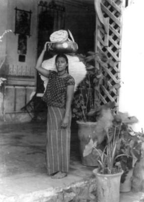 Mujer vendedora de tostadas en el portico de una casa