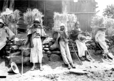 Cargadores descansando en una barda de piedra, retrato de grupo, reprografía