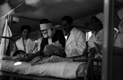 Federico Gómez, doctor, y enfermeras observan a un niño recibiendo un regalo de navidad en el Hospital