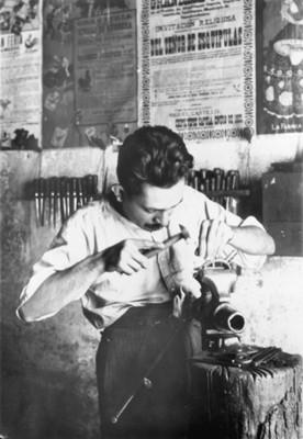 Hombre haciendole grabados a unas espuelas