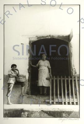 Mujer y niño posan en la puerta de su casa, retrato