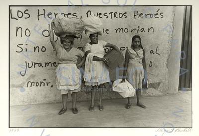 Mujeres cargan bultos frente a muro con propaganda política, retrato