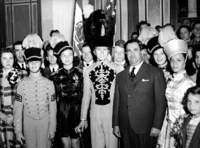 Manuel Ávila Camacho acompañado por adolescentes, en un salón, retrato de grupo