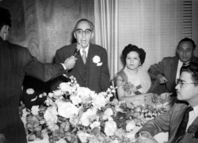 Juanita Guerra, publicista junto a un orador, durante un banquete