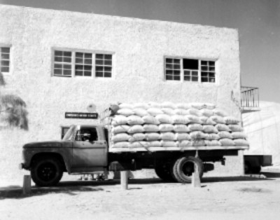 Chofer junto a un cami'pn de carga, en la ventanilla de un almacén de depósito