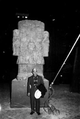 Hombre de pie frente al monolito de la Cuatlicue en el Museo Nacional de Antropología