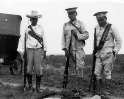 Miembros de pelotón de fusilamiento junto a un cadáver