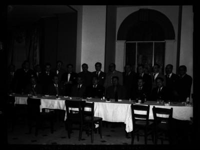Rafael Olmos acompañado de otros funcionarios durante un banquete en su honor, retrato de grupo